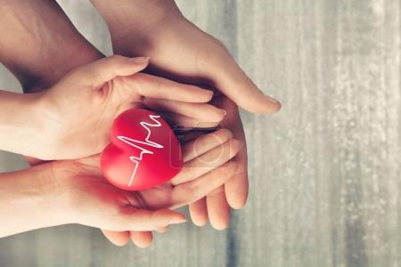 Man and woman holding red heart