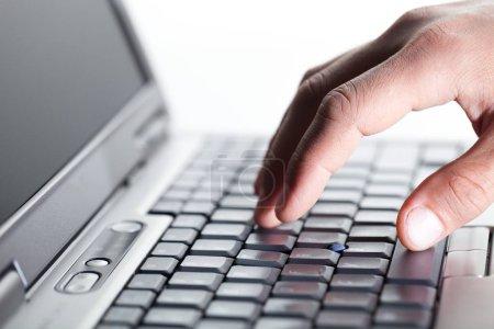 Hand typing on keyboard on modern laptop