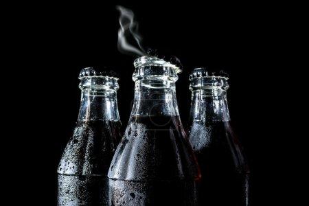 Photo pour Bouteilles en verre de soude avec fumée, gaz, vapeur isolée sur fond noir - image libre de droit