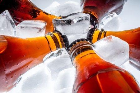 Photo pour Bouteilles en verre de soude dans un glaçon réfrigéré sur un fond clair - image libre de droit