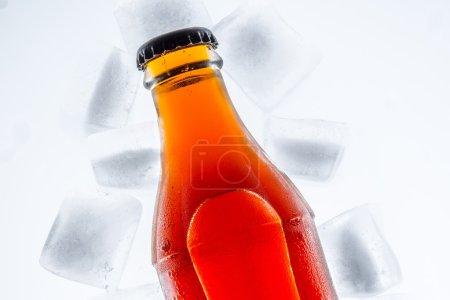 Photo pour Bouteille en verre de soude dans un glaçon réfrigéré sur un fond clair - image libre de droit