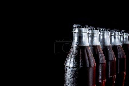 Photo pour Bouteilles en verre de soude debout dans une rangée isolée sur un fond noir - image libre de droit