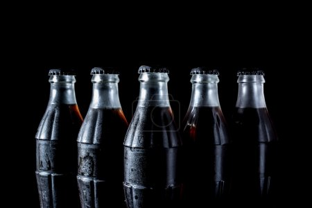 Photo pour Bouteilles en verre de soude isolées sur fond noir - image libre de droit