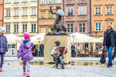 Warsaw, Poland  May 07, 2017: Children run around the street musician in the old town in Warsaw near the mermaid sculpture. Mermaid is a symbol of Warsaw. The Poles call it a sirenka.