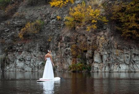SUP the girl in a white dress with a paddle board ...
