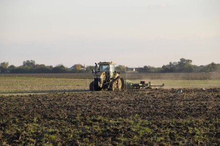 Tractor plowing plow the field. Tilling the soil in the fall after harvest. The end of the season.