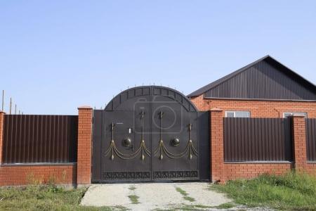 Photo pour Maison en brique avec une clôture et des portes. Vue d'une nouvelle clôture construite et d'une maison en briques et en métal ondulé - image libre de droit