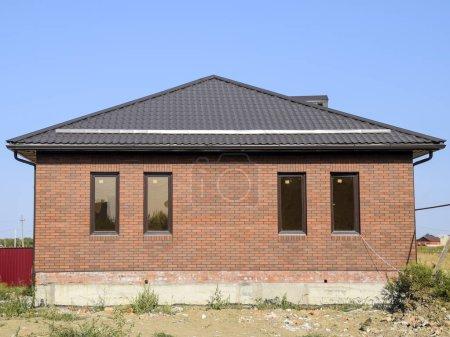 Photo pour Toit brun et brique brune. La maison avec des fenêtres en plastique et un toit en tôle ondulée. Toiture de profil métallique ondulé sur la maison avec fenêtres en plastique . - image libre de droit
