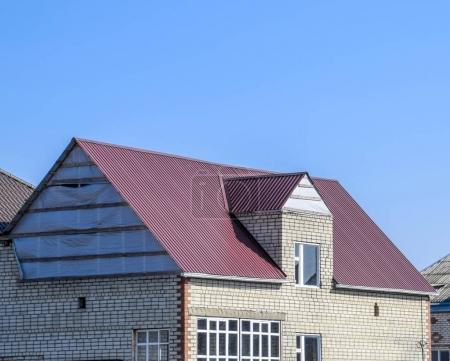 Photo pour Maison du bloc de cendres. La maison avec des fenêtres en plastique et un toit en tôle ondulée. Toiture de profil métallique ondulé sur la maison avec fenêtres en plastique . - image libre de droit