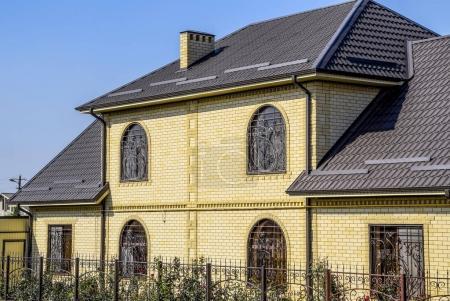 Photo pour Maison de brique jaune et toit ondulé brun en métal. Lattices sur les fenêtres - image libre de droit