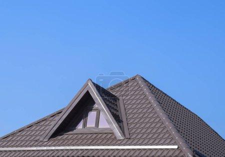 Photo pour Maison avec fenêtres en plastique et un toit brun de tôle ondulée. Toiture de profil métallique ondulé sur la maison avec fenêtres en plastique . - image libre de droit