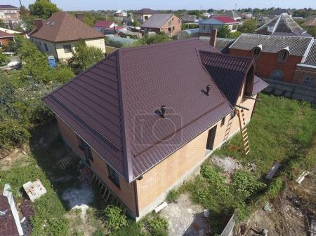 Photo pour Le toit de tôle ondulée. Toiture de profil métallique forme ondulée. Maison avec un nouveau toit métallique . - image libre de droit