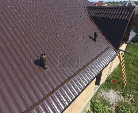 Photo pour Le toit de tôle ondulée. Toiture de profil métallique forme ondulée. conduits d'air sur le toit métallique . - image libre de droit