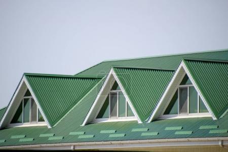 Photo pour La maison avec des fenêtres en plastique et un toit vert de tôle ondulée. Toiture de profil métallique ondulé sur la maison avec des fenêtres en plastique. Toit vert de profil en métal ondulé et fenêtres en plastique. - image libre de droit
