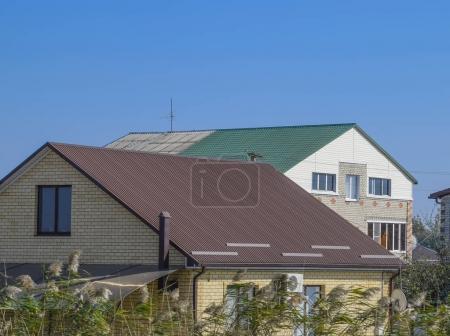 Photo pour Maisons avec toits en métal ondulé. Toit brun et vert. Matériaux modernes pour toiture - image libre de droit