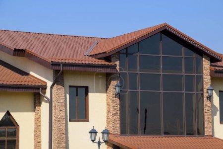 Photo pour Bâtiment avec des murs jaunes et un toit rouge-brun. Matériaux modernes de finition et de toiture - image libre de droit
