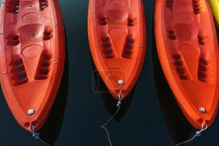 Red kayaks on dark blue water