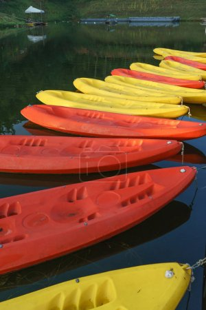 Pattern of yellow and red kayaks on dark water