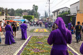 Purple robed man standing in front of flower carpets looking at the procession of San Bartolome de Becerra in 1a Avenida, Antigua, Guatamala