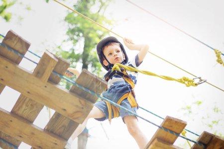 Kids climbing in adventure park. Boy enjoys climbing in the rope