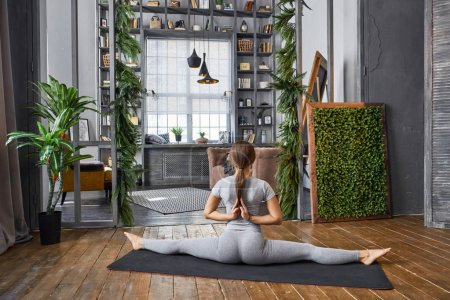 Woman practicing advanced yoga in the living room