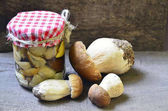 Marinated mushrooms in a glass jar and fresh Boletus edulis mushrooms on old wooden table.