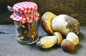 Dried mushrooms in a glass jar and fresh Boletus edulis mushrooms on old wooden table.