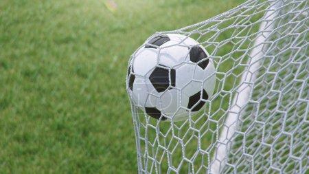Photo pour Illustration 3D Ballon de football a volé dans le but. Ballon de football plie le filet, sur le fond d'herbe. Ballon de football dans le filet de but sur fond d'herbe. Un moment de délice . - image libre de droit