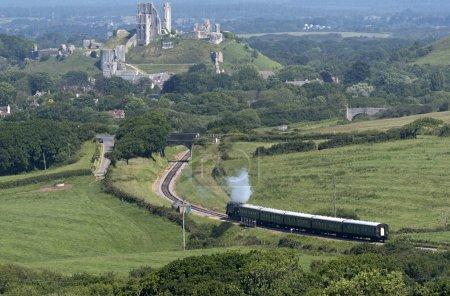 A passenger vintage steam train passing through Dorset countryside UK