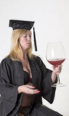 Mature student wearing a hat with gown and holding a glass of wine