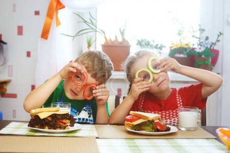 Children make sandwiches in the kitchen . Brother and sister sandwiches .The concept of fast food