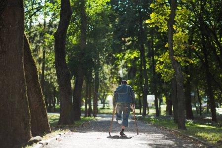 Photo pour Homme sans-abri handicapé sans une jambe promenades dans le parc de la ville seul. Homme avec une jambe amputée utilise deux béquilles en bois. - image libre de droit