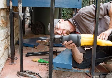 Photo pour Travailleur de la construction en utilisant un mouvement alternatif scie pour découper le poteau de fer forgé. - image libre de droit