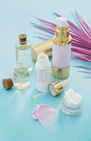 natural skincare beauty products with pink palm leaf on blue background