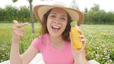 Šťastná žena v zahradě se bude pít pomerančový džus