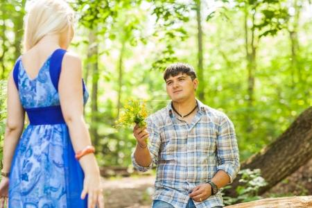 Young man giving a flower dandelion to girlfriend outdoors