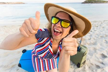 Happy laughing woman tourist with suitcases showing thumbs up gesture. Travel and summer vacation concepts.