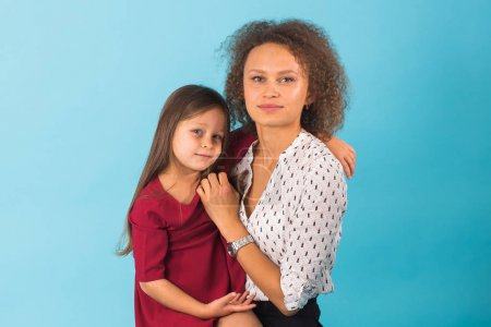Happy mother and daughter hugging and smiling at camera isolated on blue