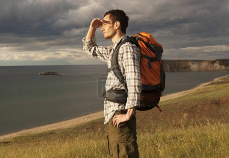 young tourist man with a backpack on the lake, Lake Baikal, summer tourist walk, freedom and happiness, beautiful wildlife