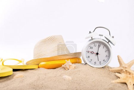 White vintage alarm clock with beach items on the sand
