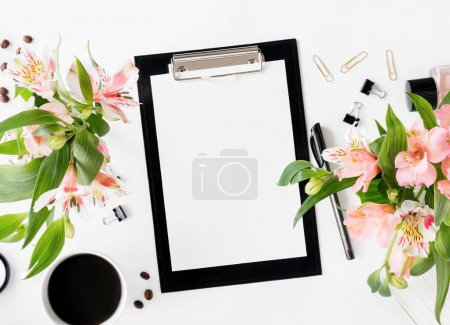 Workspace with clipboard, office accessories, cup of coffee and bouquet of flowers. Flat lay, top view