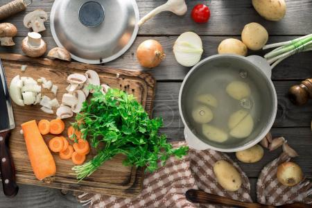 Raw ingredients for cooking vegetarian soup on wooden table