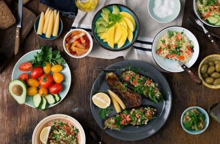 Photo for Set of dishes for a healthy food on wooden table, top view. Stuffed eggplants, salad with bulgur, fruits and vegetables - Royalty Free Image