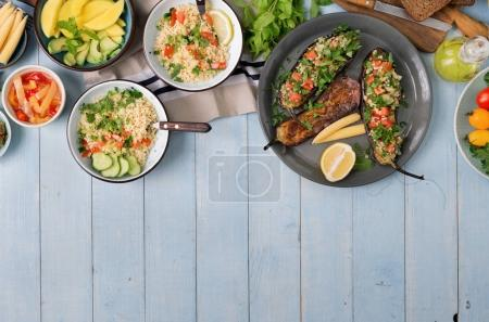 Photo for Set of dishes for healthy food on wooden table with border, top view. Stuffed eggplants, salad with bulgur, fruits and vegetables - Royalty Free Image