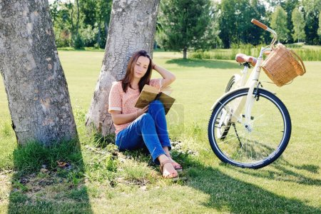 Image of young happy woman sitting under a tree wi...