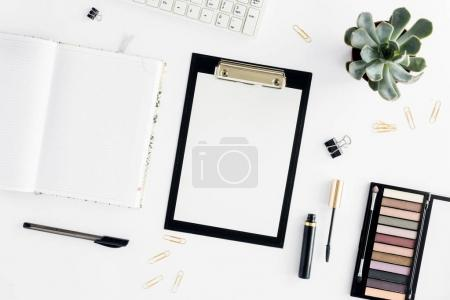Photo for Home office workspace. Feminine workplace with clipboard, eyeshadow, mascara, keyboard and notepad. Office table desk. Top view. Flat lay - Royalty Free Image