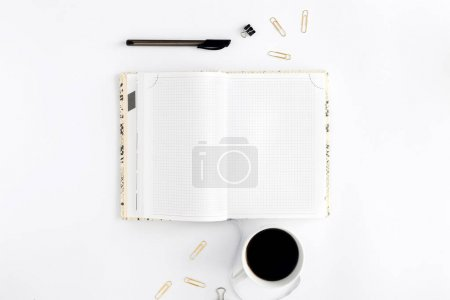 Photo for Open feminine notepad with cup of coffee on white background. Top view. Flat lay. Concept of feminine workplace - Royalty Free Image