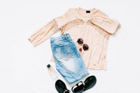Photo pour Chemisier rose, jeans, sandales, parfum, rouge à lèvres et lunettes de soleil sur fond blanc. Concept de blog beauté. Pose plate. Vue du dessus - image libre de droit