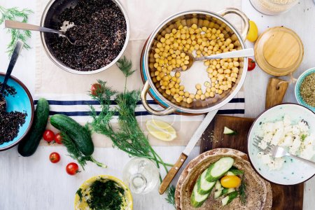Photo for Ingredients for cooking healthy salad with black quinoa, chickpea, feta cheese and vegetables on wooden table, top view. Healthy food concept - Royalty Free Image