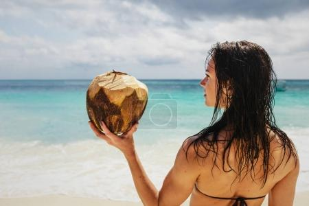 Beautiful woman on the ocean shore holding fresh coconut